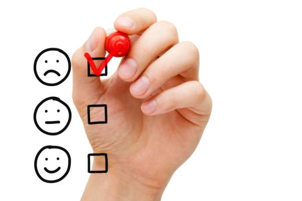 Hand putting check mark with red marker on poor customer service evaluation form.